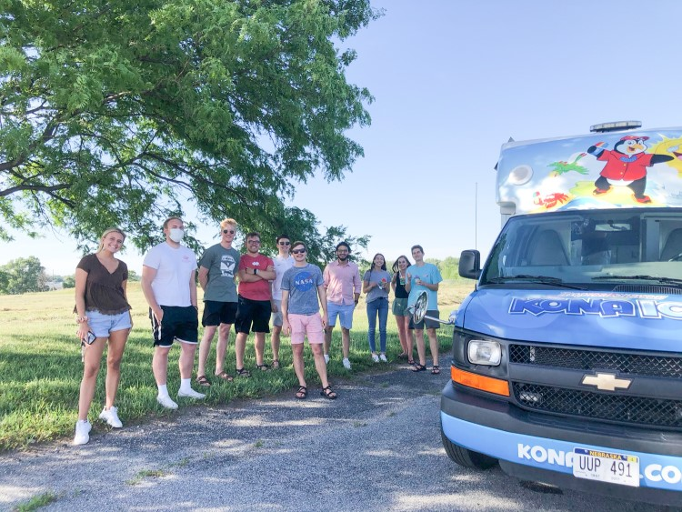 Interns from Spreetail stand near a vehicle on a company outing