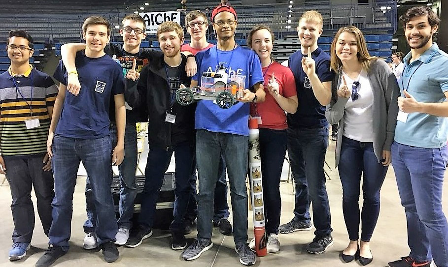 Group of students holding a trophy for a competition they placed first in.