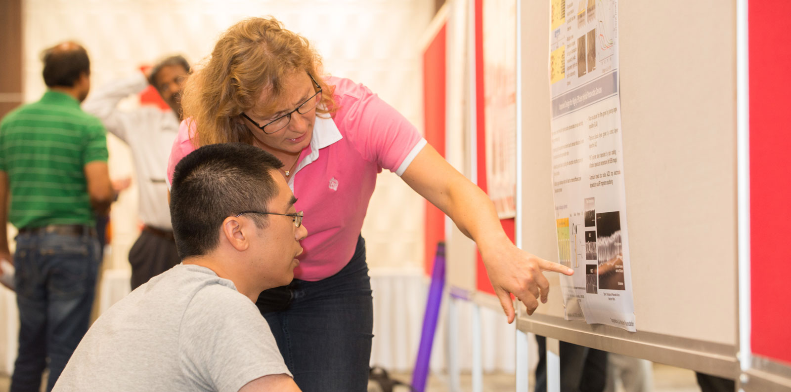 Dr. Eva Schubert discusses a poster with a colleague.