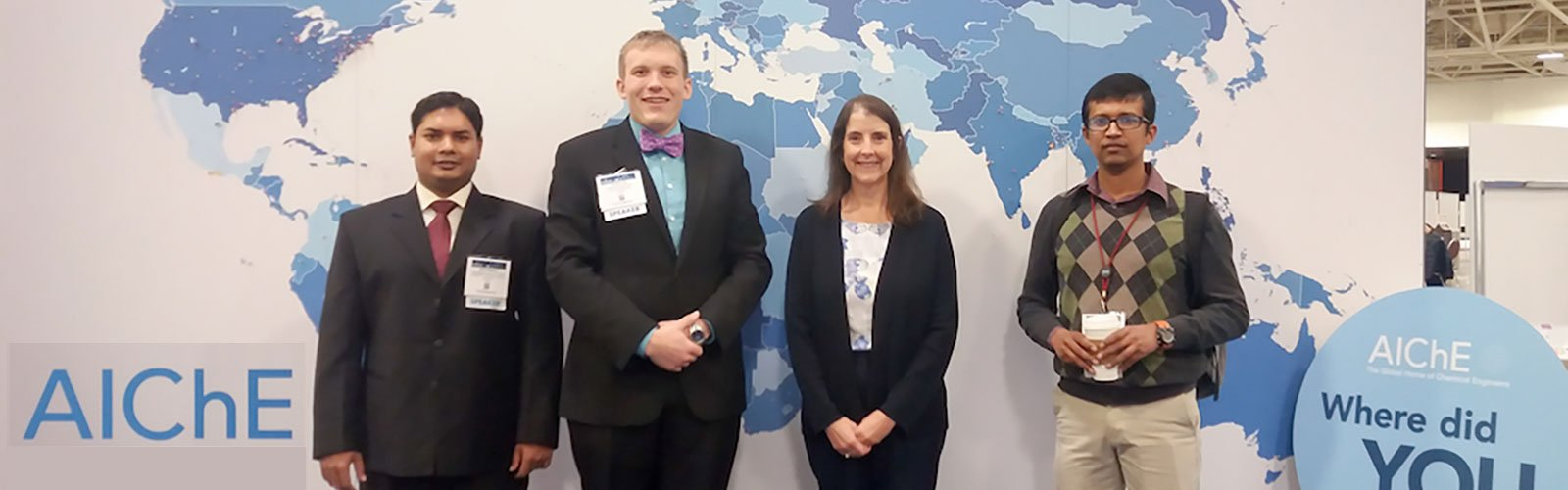 Three graduate students and thier professor posing in front of a map.