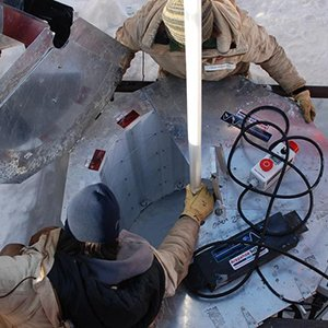 The WISSARD research team set up an ultraviolet light collar at the top of the bore hole in Antarctica. (Photo by Frank Rack, UNL Science Management Office)