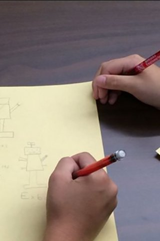 Kids drawing a robot on a piece of paper