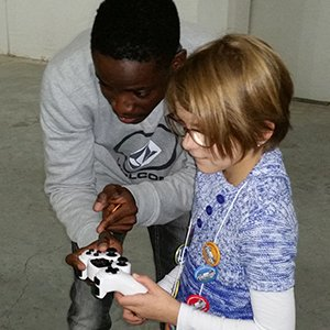 Daryl Dodoo, a junior computer engineering major, explains how to work the controls of a robot to 9-year-old Mia Vogel during the Nebraska Robotics Expo on Feb. 21 at the Strategic Air Command Museum.