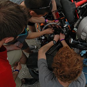 Husker Motorsports team members work to repair the car on June 19 after its clutch pin was sheared.