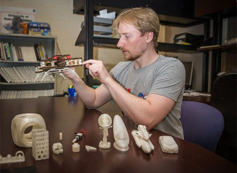 University of Nebraska-Lincoln mechanical engineering graduate student Matthew Mahlin displays some objects made by a 3D printer in the lab.
