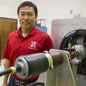 Jie Cheng, doctoral student in electrical engineering, stands next to the partial prototype of a wind turbine system that research suggests could yield 8.5 percent more electricity than conventional counterparts. (Troy Fedderson / University Communications)