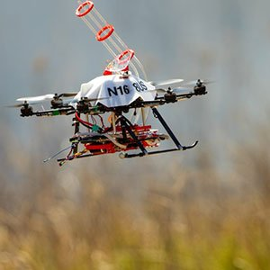 A UNL-designed drone returns to the side of a burn area for a reload of fireballs and the chemical to make them burn. The balls are carried aloft in the tubular structure atop the drone. The ball carries a chemical powder and, while airborne, the drone injects a second chemical. The drone then drops the ball and it bursts into flames within 60 seconds. (Craig Chandler / University Communications)
