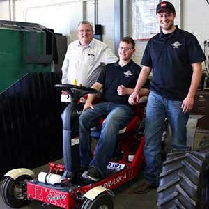Roger Hoy (from left), Caleb Lindhorst and Luke Prosser show off a tractor designed by students for a 2014 engineering competition. Lindhorst was involved in a December 2013 auto accident and support from Hoy and Prosser has helped him return to classes at UNL. (Photo by Troy Fedderson / University Communications)