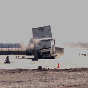 An 80,000-pound tractor-trailer crashes during a test of a concrete barrier on April 13 at the Midwest Roadside Safety Facility.