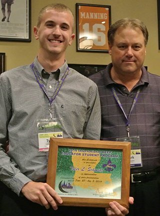 UNL Construction Management graduate student Tyler Schmidt receives a plaque after taking first place in student presentations at the IHEEP 2014 Convention in New Orleans.