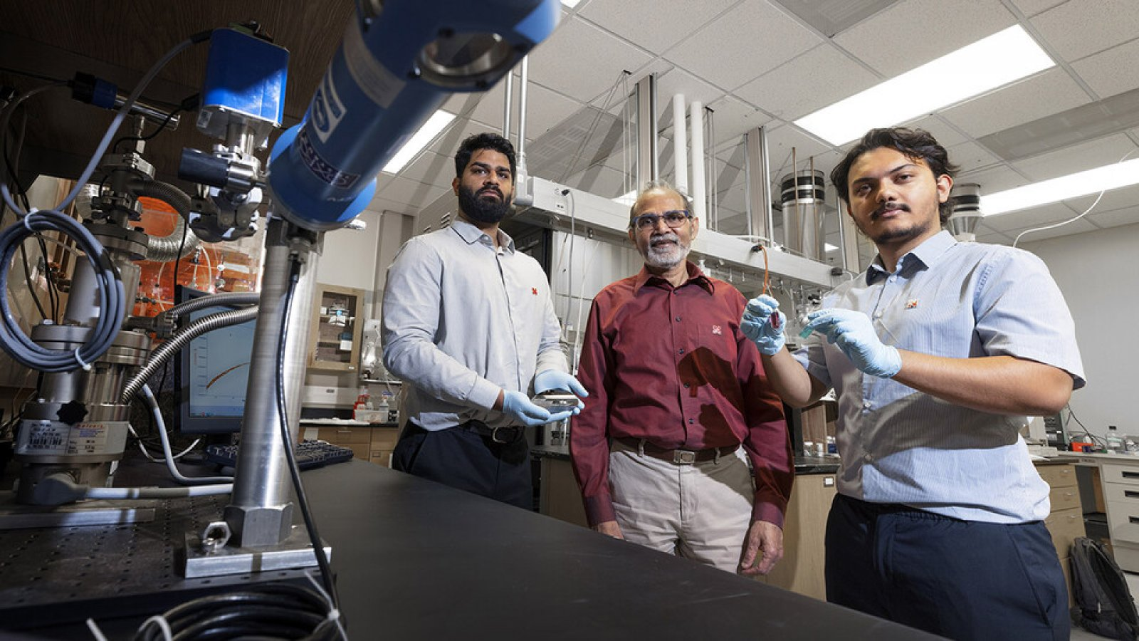 Abhijeet Prasad (left), a doctoral student in engineering; Ravi Saraf (center), Anderson Distinguished Professor of chemical and biomolecular engineering; and Aashish Subedi, a senior physics major, are photographed in Saraf's Othmer Hall lab. Prasad is holding small electronic chips used to study the nanoparticle necklace network devices. Subedi is holding a suspension of nanoparticle necklaces (blue container) made from individual particles (red container). (Craig Chandler / University Communication)