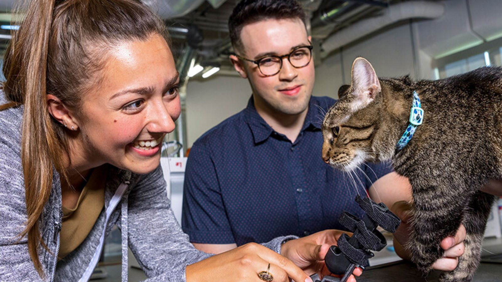 Recent Husker graduate Abby Smith (left) holds a prosthetic prototype that she and senior Harrison Grasso (center) helped develop for Olive (right), who is missing part of her left foreleg. (Craig Chandler / University Communication)