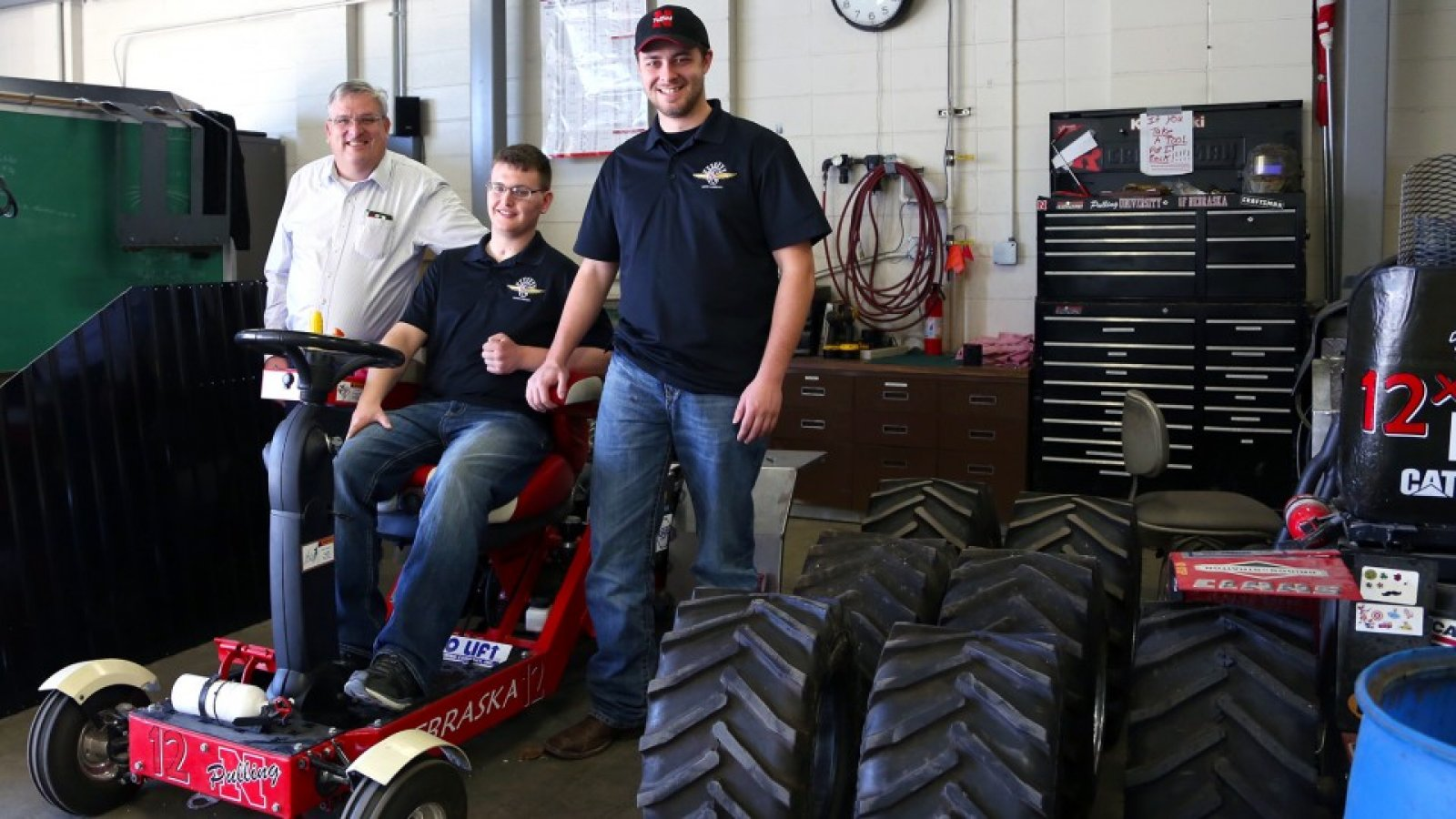 Roger Hoy (from left), Caleb Lindhorst and Luke Prosser show off a tractor designed by students for a 2014 engineering competition. Lindhorst was involved in a December 2013 auto accident and support from Hoy and Prosser has helped him return to classes on campus. For his work supporting Lindhorst and other students, Hoy has received the James V. Griesen Exemplary Service to Students Award.