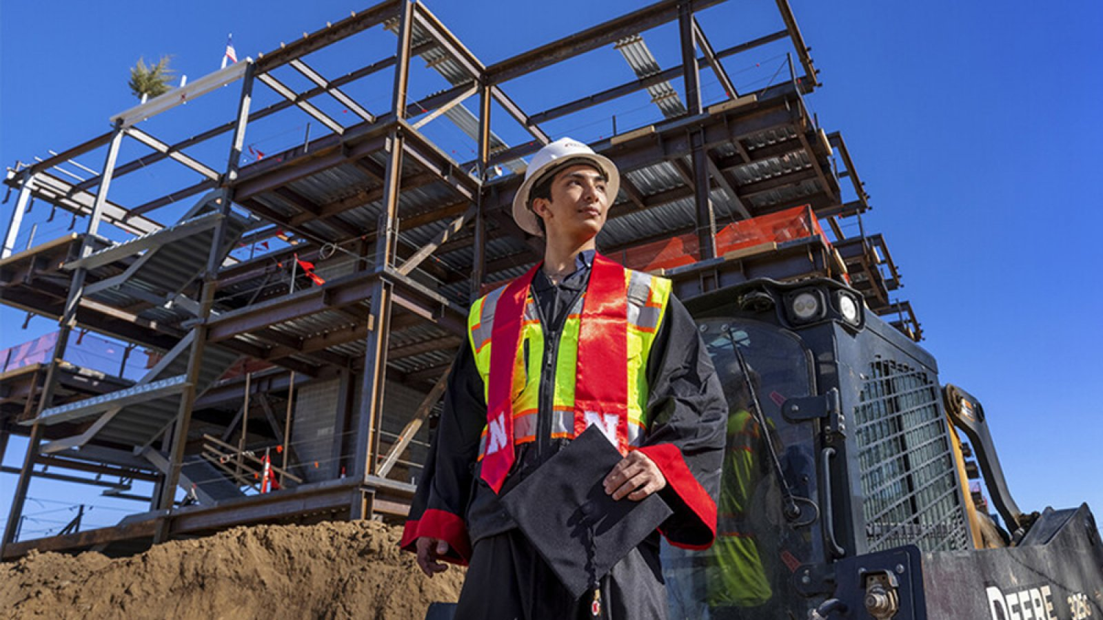 Yajyoo Shrestha, a graduating senior in civil engineering, stands before the construction site of the new College of Education and Human Sciences building on City Campus. (Craig Chandler / University Communication)