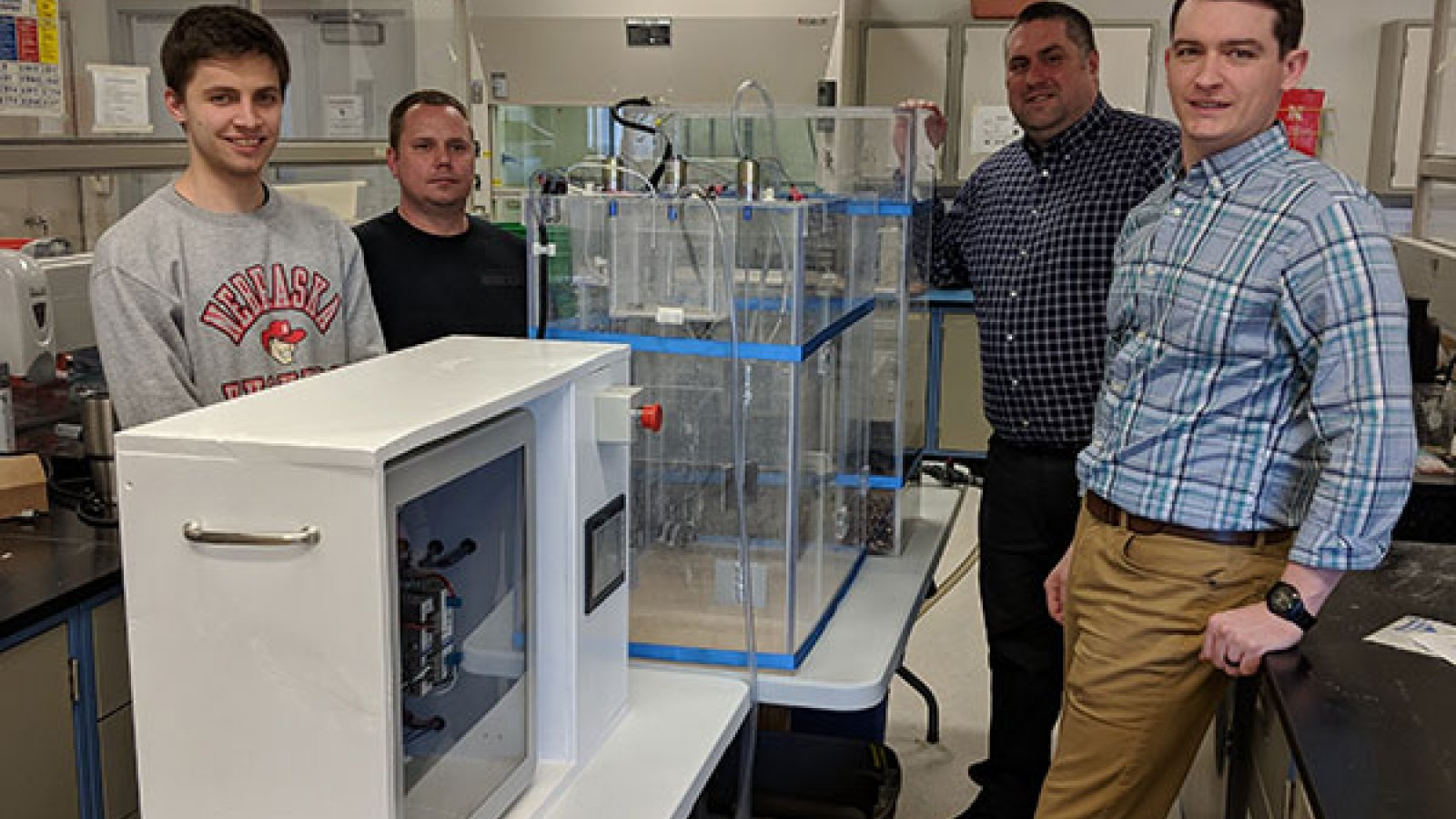 As a unique collaboration between civil engineering and electrical and computer engineering departments - students John Strudl (left), Derek Nelsen (second from left), Jacob Eckstrom (right) and Isaac Knutson (not pictured) and senior design instructor George Hunt (second from right), assistant professor of practice in civil engineering - created a working model of a water treatment plant that could be used for K-12 and general public outreach.